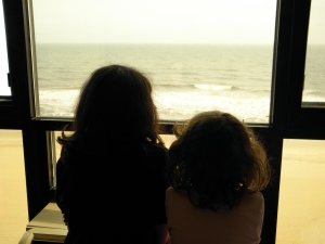 Two girls looking out the window at the beach.