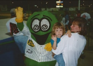 Pickle Mascot and child waving at camera
