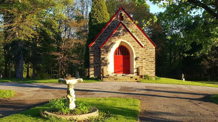 Small church in the woods with red door