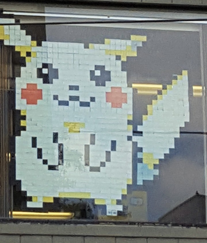Pokémon's Pikachu made out of sticky notes in the 2nd floor window of a library.