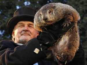 Groundhog being held aloft by man in top hat