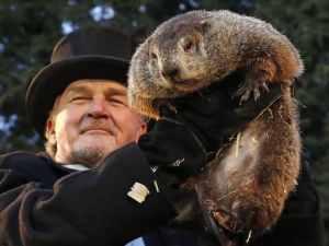 Groundhog being held aloft by man in top hat