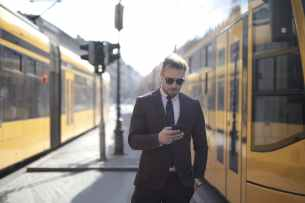 confident businessman using smartphone on street